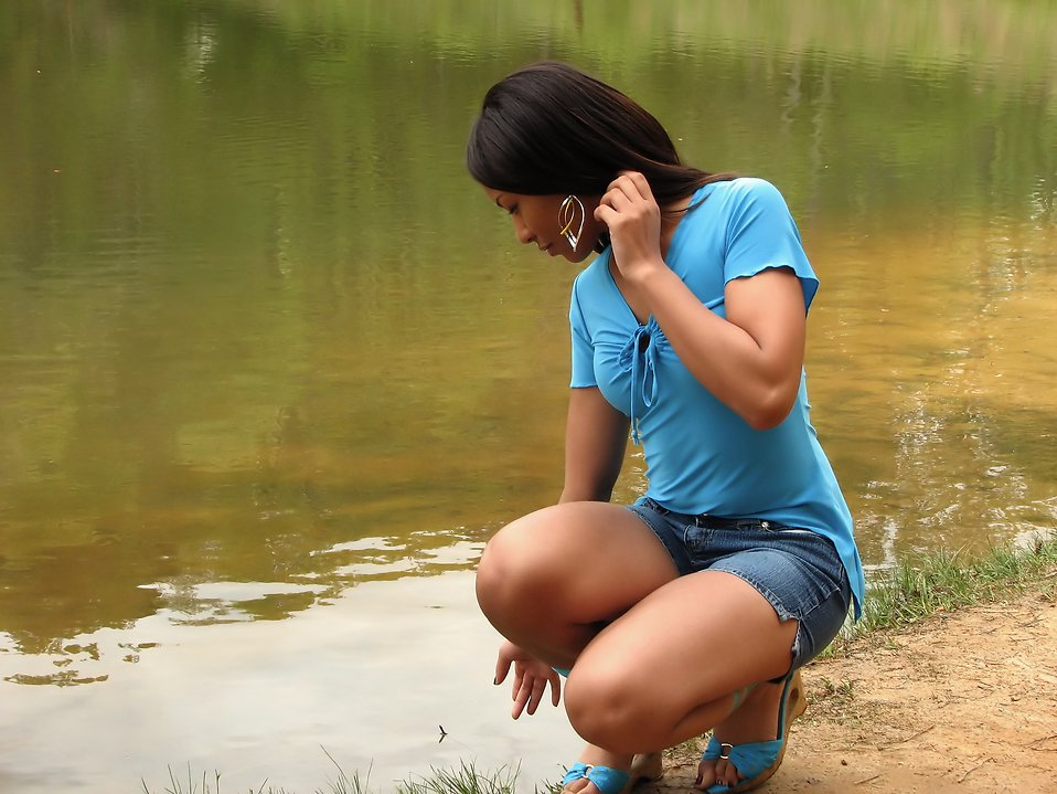 A beautiful African American teen girl posing near a lake : Free Stock Photo