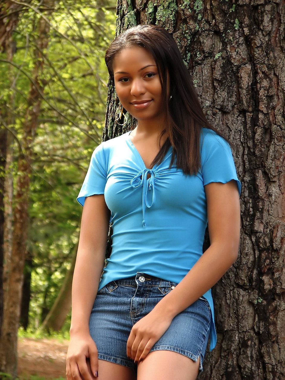 A beautiful African American teen girl posing against a tree in the woods : Free Stock Photo