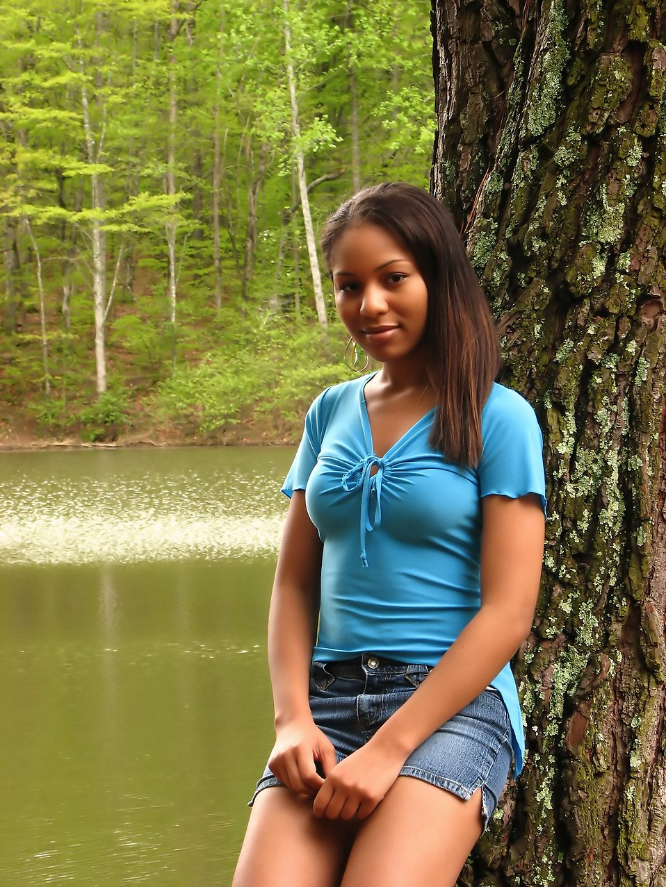 A beautiful African American teen girl posing against a tree by a lake : Free Stock Photo