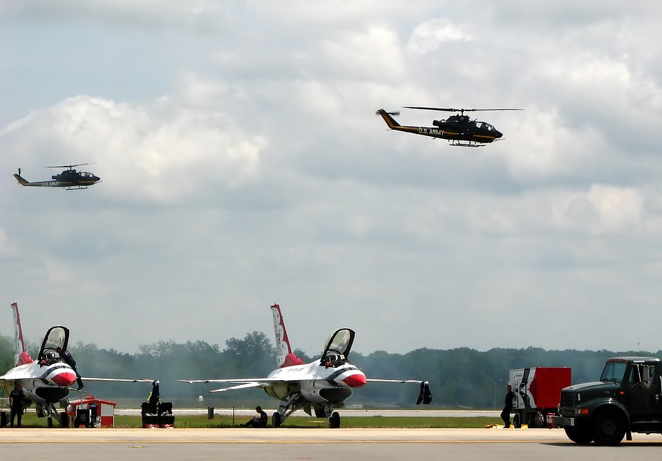 AH-1F Cobra attack helicopters flying in the sky over a runway with Thunderbird jets : Free Stock Photo