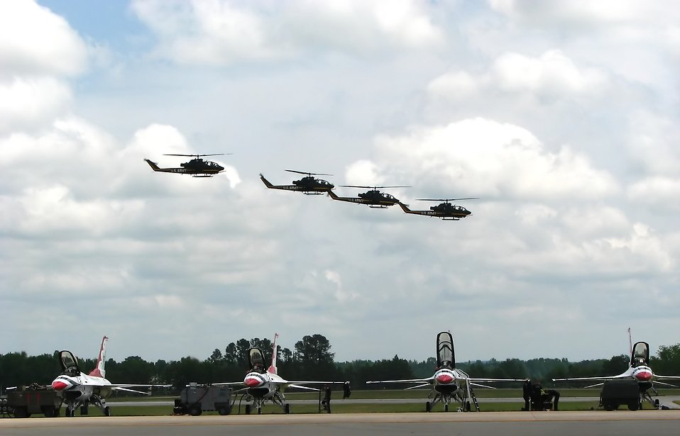 AH-1F Cobra attack helicopters flying over a runway with Thunderbird jets : Free Stock Photo