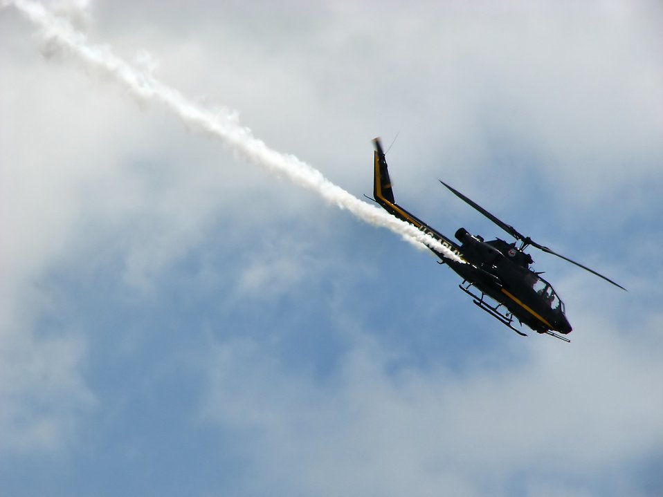 An AH-1F Cobra attack helicopter flying in the sky with a smoke trail : Free Stock Photo