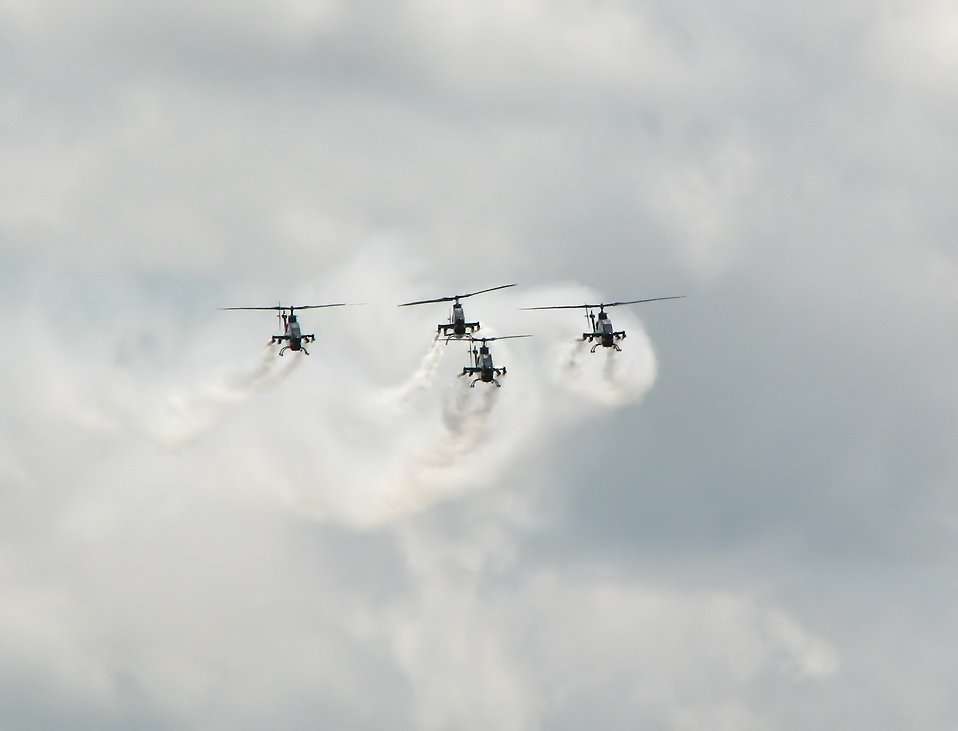Four AH-1F Cobra attack helicopters flying with smoke trails in the sky : Free Stock Photo