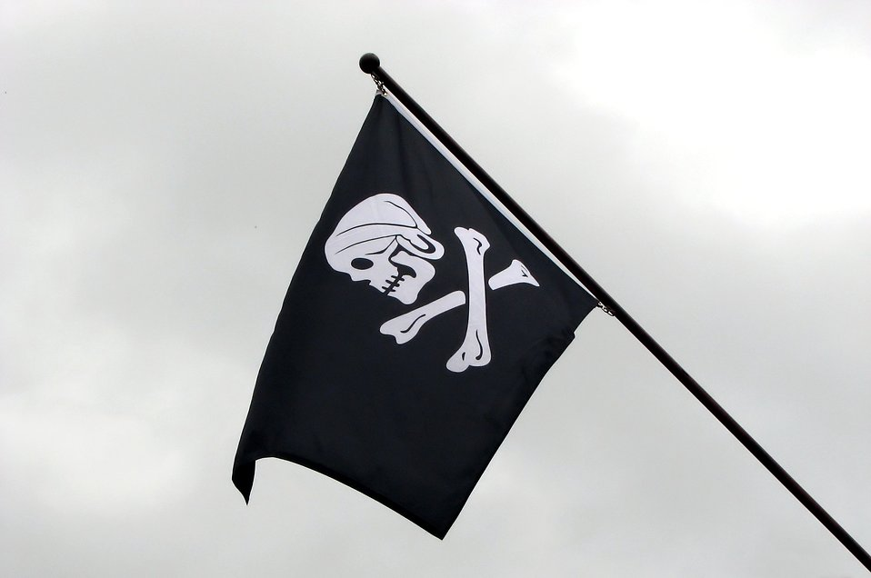 A skull and crossbones pirate flag flying in the sky : Free Stock Photo