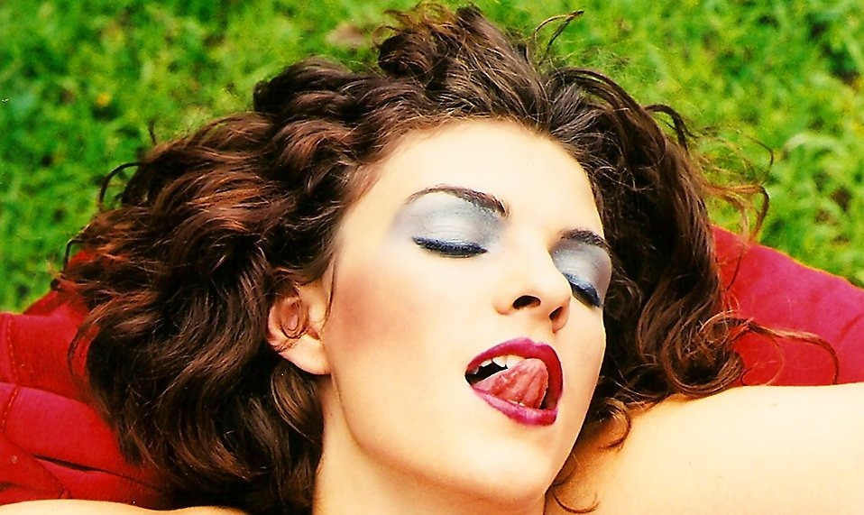 Close-up portrait of a beautiful woman licking her lips : Free Stock Photo