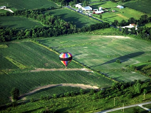 A hot air balloon flying over fields : Free Stock Photo