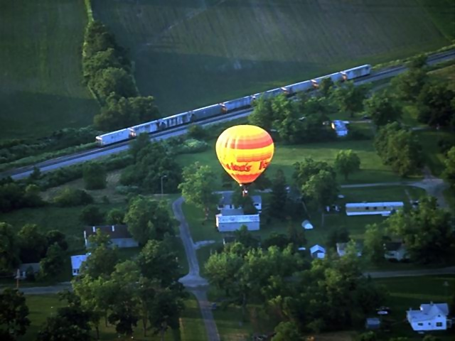 A hot air balloon flying by a train : Free Stock Photo