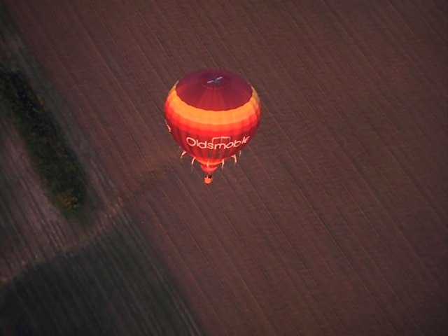 A hot air balloon flying over a field : Free Stock Photo