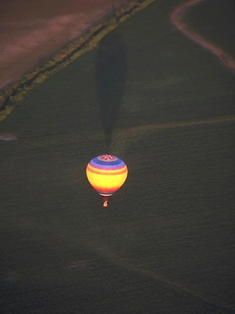 A hot air balloon flying over a field.