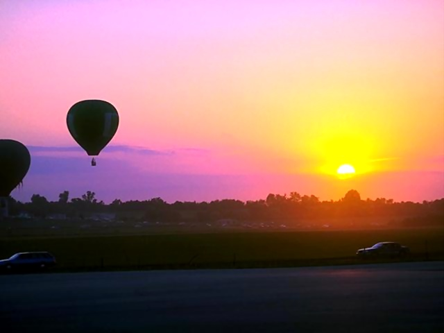 Hot air balloons flying by a sunset.