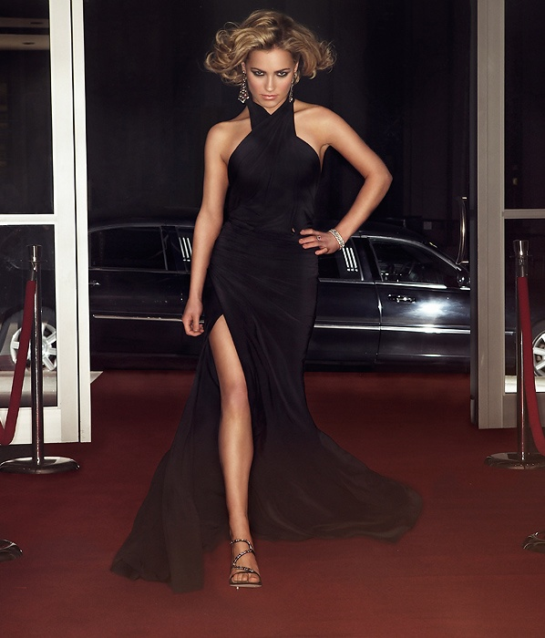 A beautiful woman walking down the red carpet with a limo in the background.