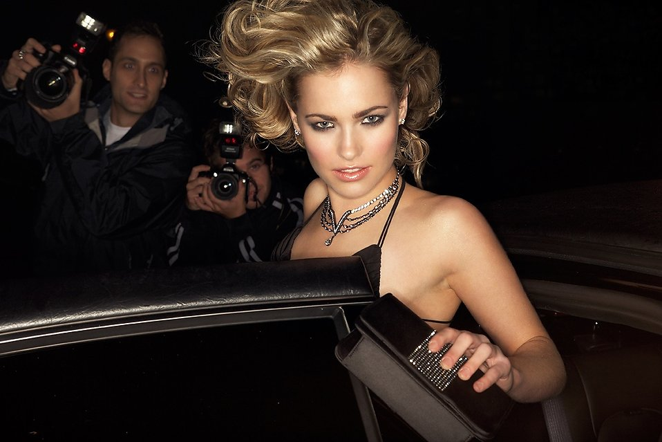 A beautiful woman entering a car surrounded by paparazzi : Free Stock Photo