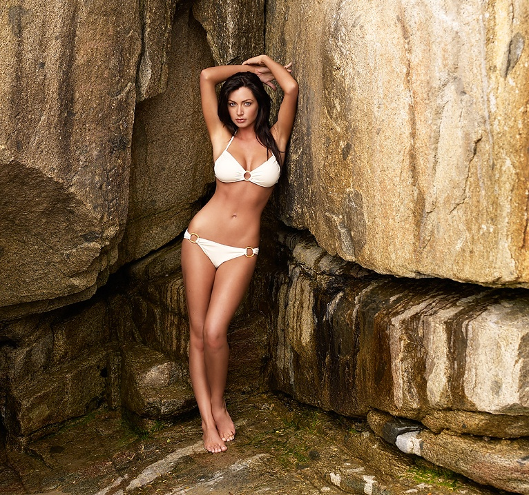 A beautiful brunette in a bikini posing on rocks : Free Stock Photo