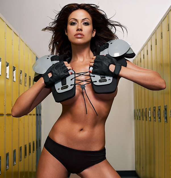 A beautiful woman posing with football gear in a locker room : Free Stock Photo