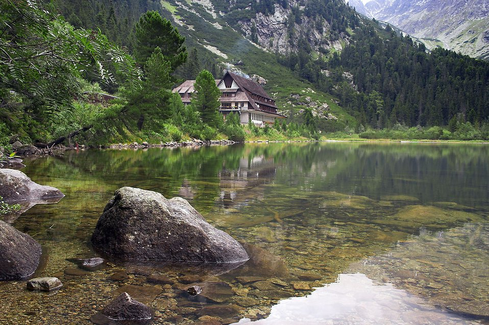 A chalet by a stream at the base of a mountain : Free Stock Photo