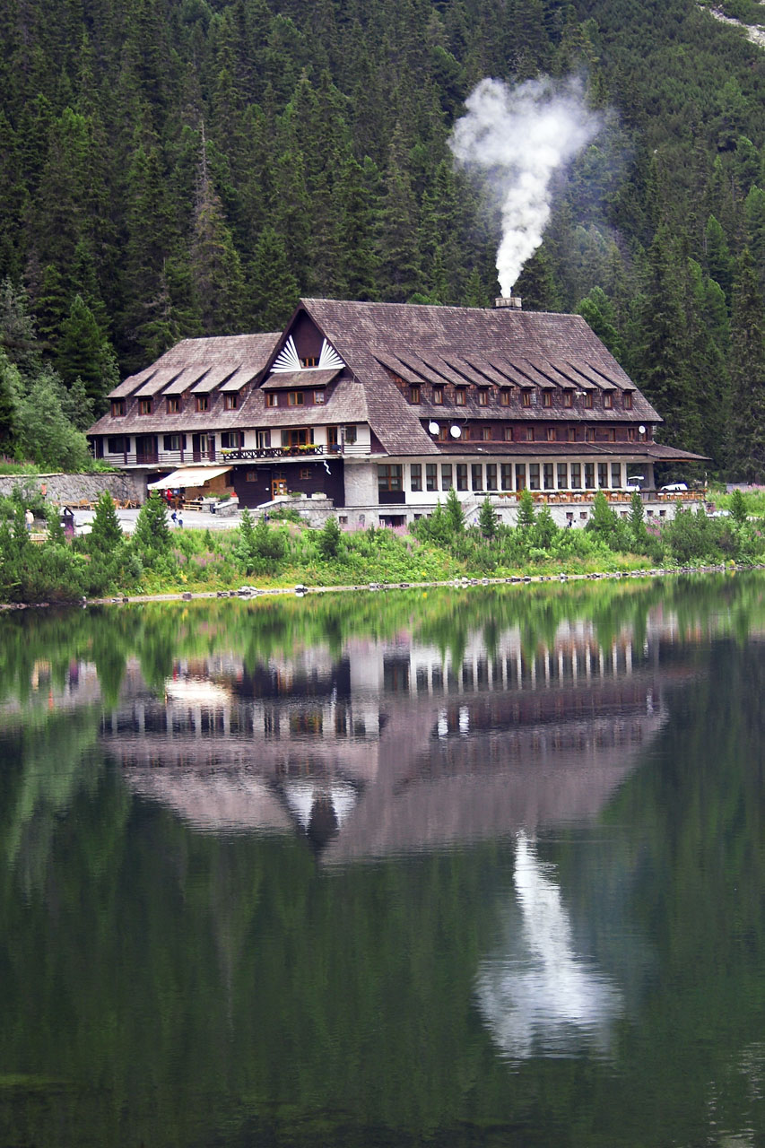 A chalet at the base of a mountain reflecting in water : Free Stock Photo