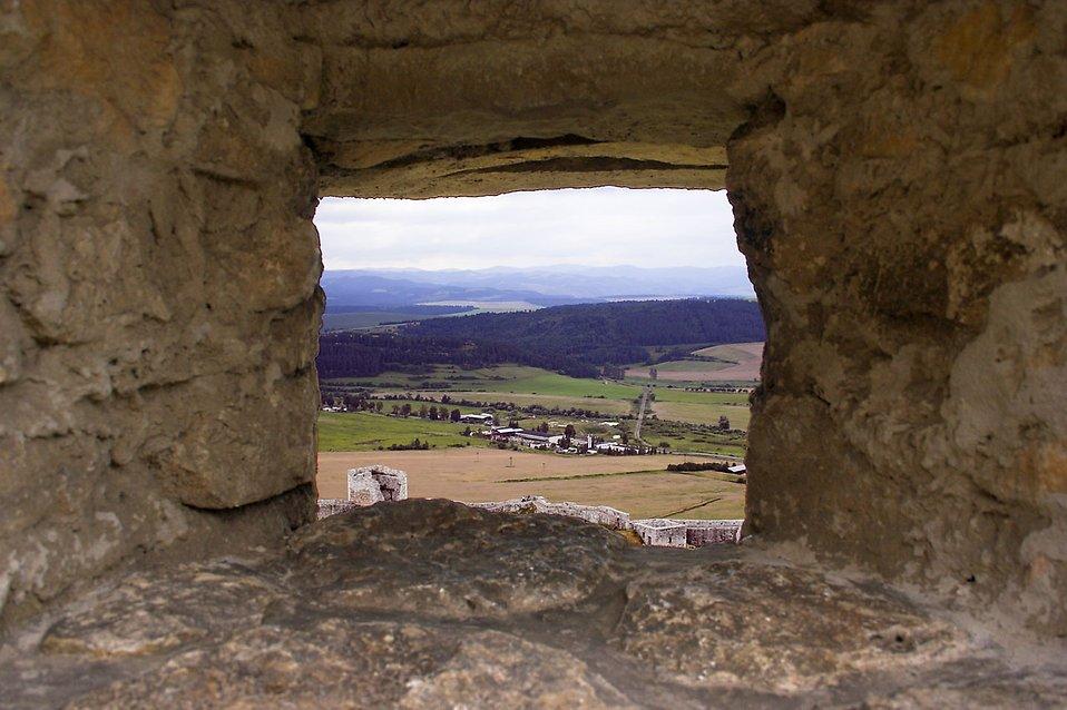 A mountain view through a stone window : Free Stock Photo