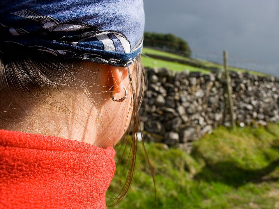 Back of a woman looking at a stone wall : Free Stock Photo