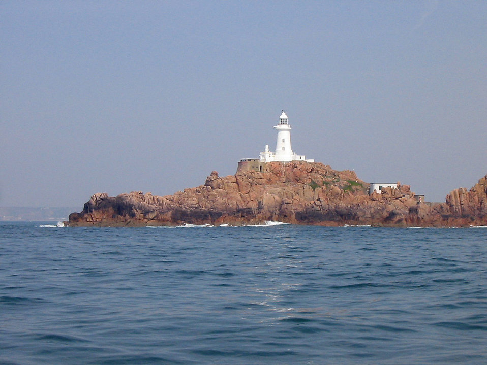 A white light house on a small rock island : Free Stock Photo