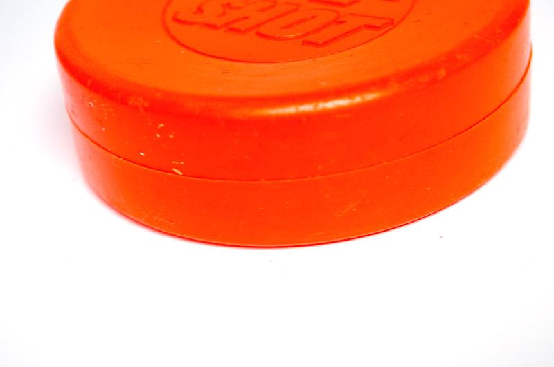An orange plastic hockey puck : Free Stock Photo
