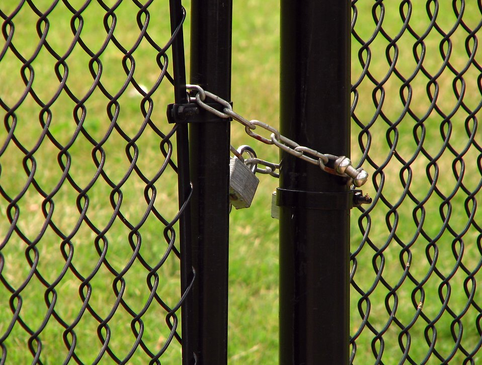 A chain and padlock on a fence by a field : Free Stock Photo