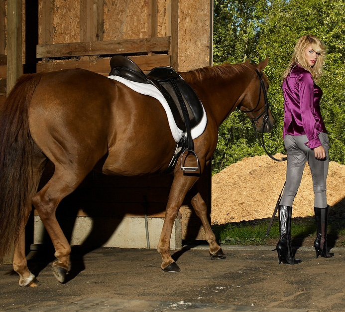 A beautiful blonde walking a horse out of a barn : Free Stock Photo