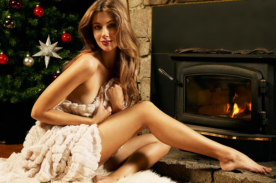A beautiful woman posing in lingerie by a fireplace and a Christmas tree : Free Stock Photo