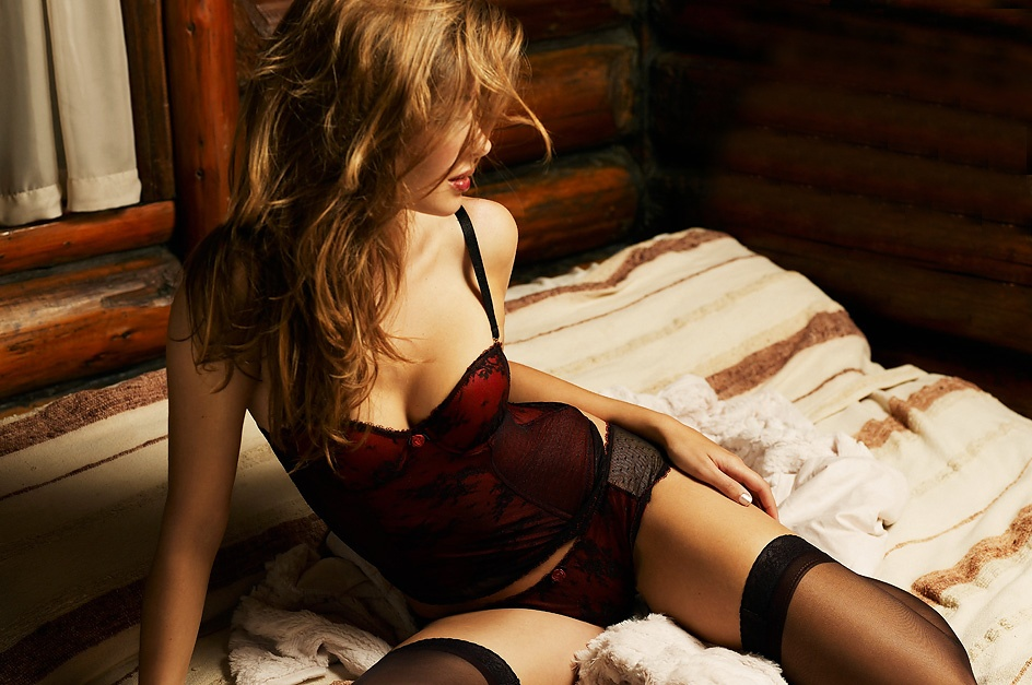A beautiful woman posing in lingerie on a bed in a log cabin : Free Stock Photo