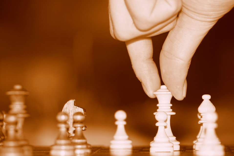 Close-up of a hand about to move a chess piece : Free Stock Photo