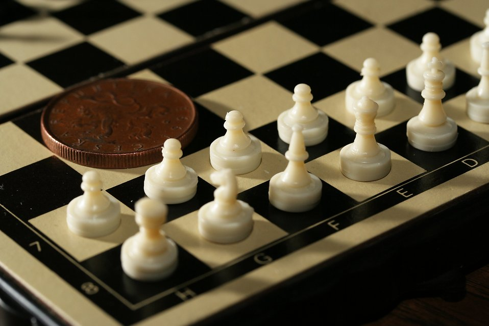 Close-up of a miniature chess set with a coin : Free Stock Photo
