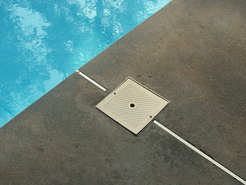 A pool filter on the edge of a pool : Free Stock Photo