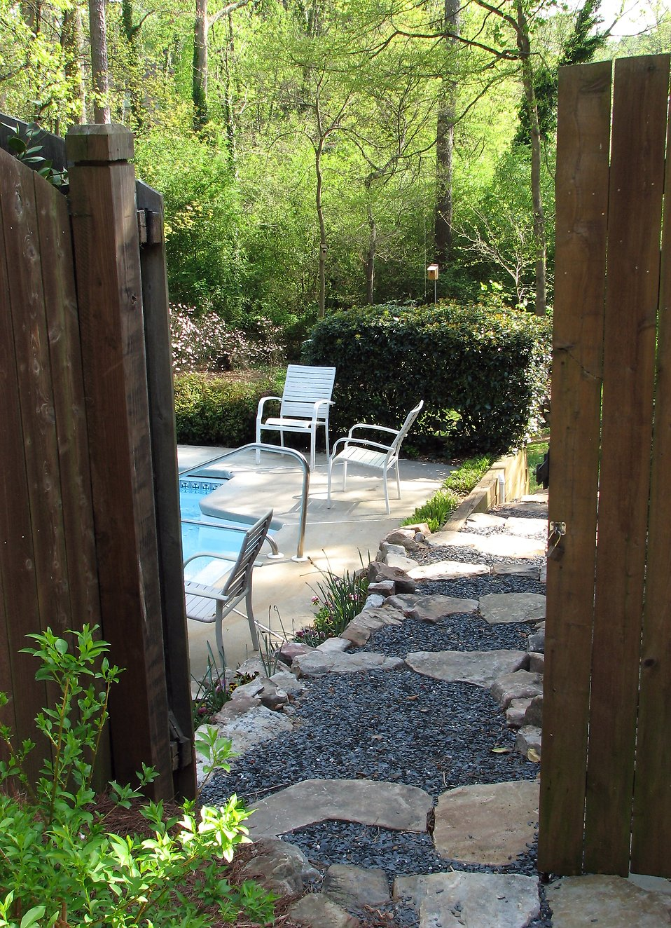 A pool and chairs in a backyard behind a fence : Free Stock Photo