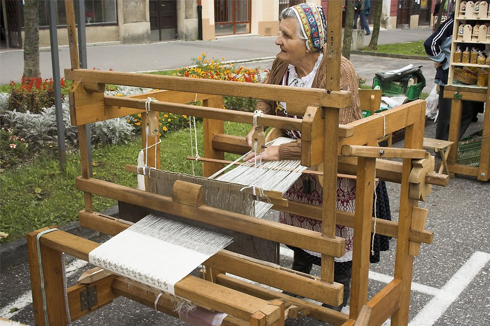 An older woman weaving in the street : Free Stock Photo