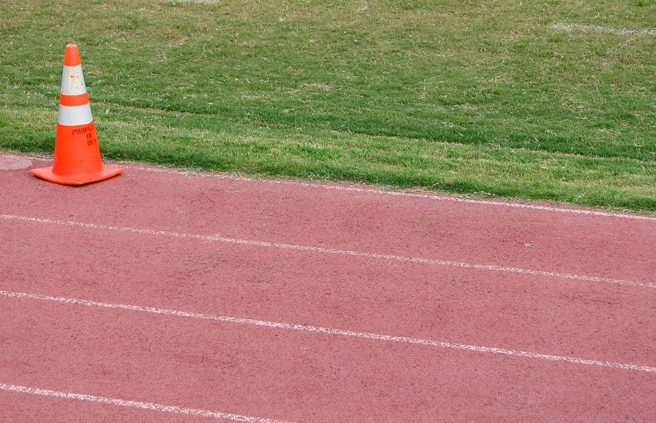 A running track by a field with an orange cone : Free Stock Photo