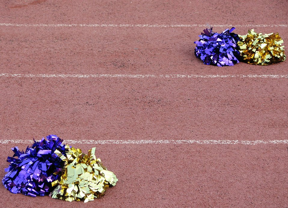Blue and gold pom poms on a track field : Free Stock Photo