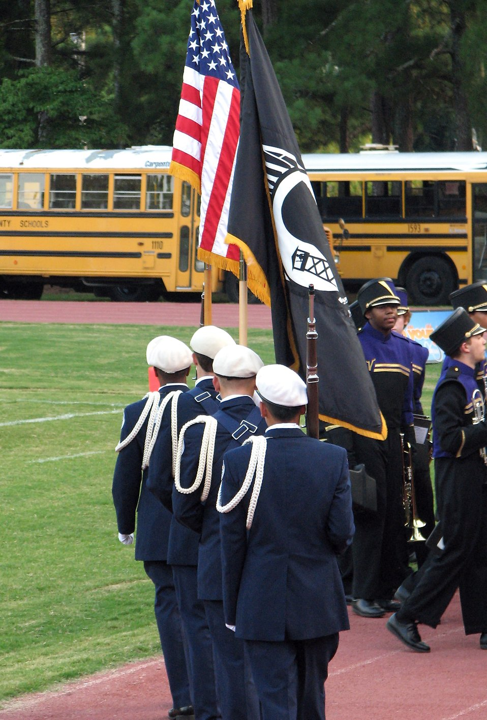 Young soldiers carrying a US flag on a football field : Free Stock Photo