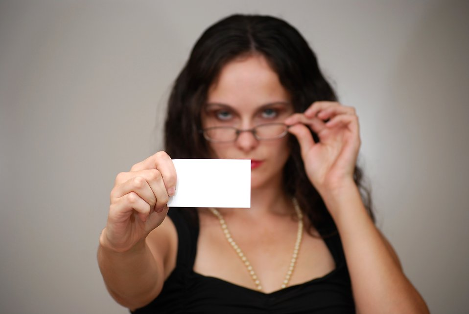 A beautiful business woman holding a blank business card : Free Stock Photo