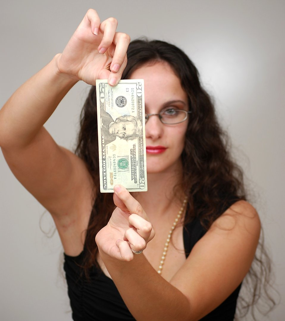 A beautiful business woman holding a twenty dollar bill : Free Stock Photo