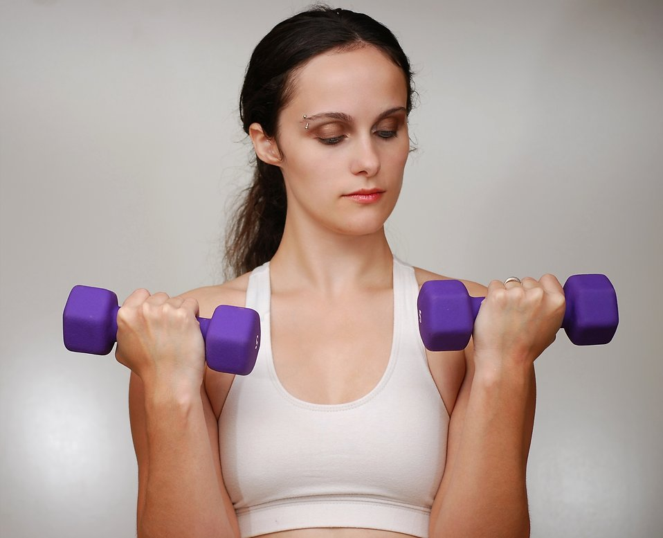 A beautiful young woman exercising with weights.