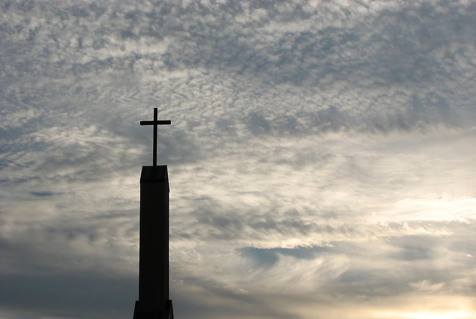 A cross before a cloudy sunset sky : Free Stock Photo