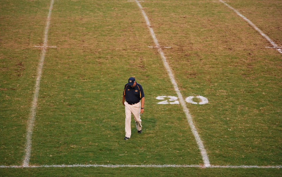 A football coach walking on an empty football field : Free Stock Photo
