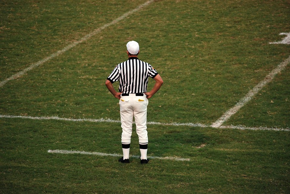 A football referee standing on an empty football field : Free Stock Photo