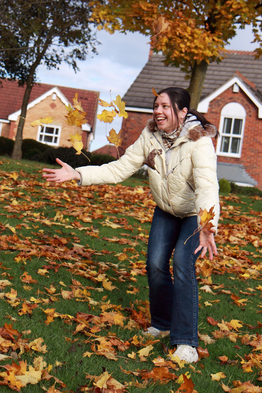 A girl playing in autumn leaves by a house : Free Stock Photo
