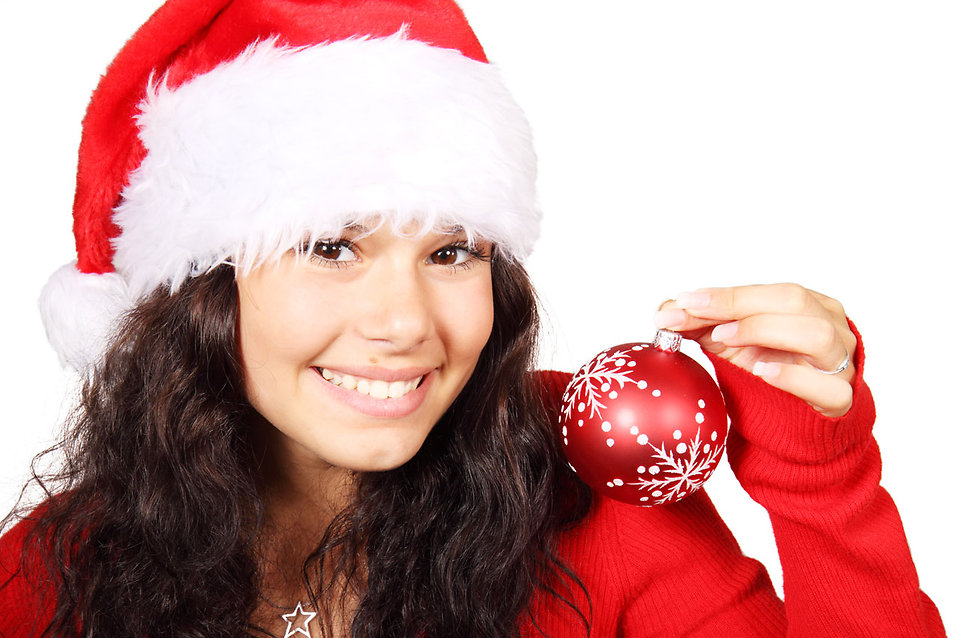 A beautiful young woman with a Christmas hat and an ornament : Free Stock Photo