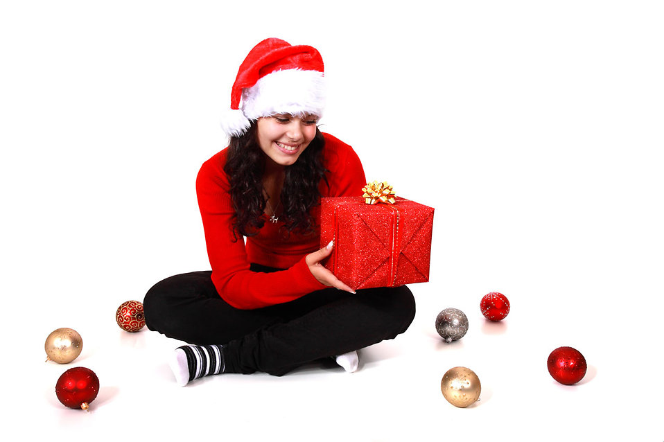 A beautiful young woman with a Christmas gift on a white background.