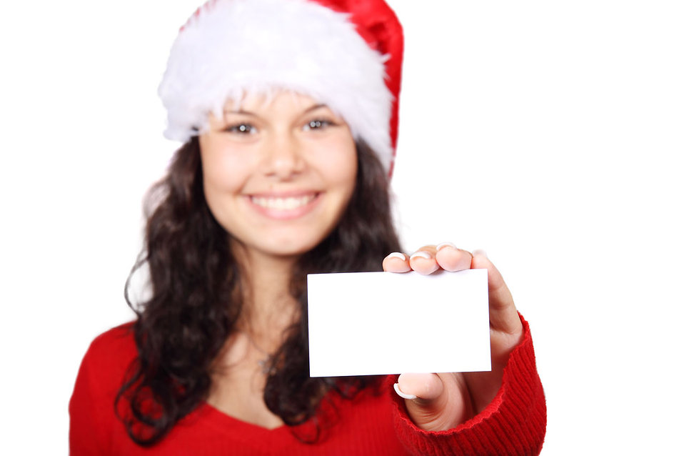 A beautiful young woman with a Christmas hat and a blank business card : Free Stock Photo
