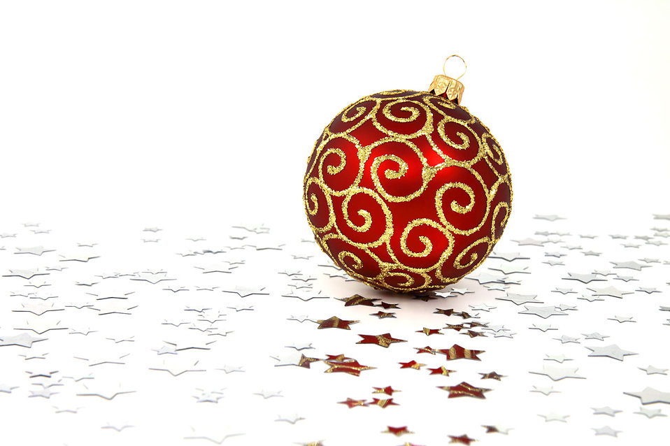 A red Christmas ornament on a white floor with silver stars : Free Stock Photo
