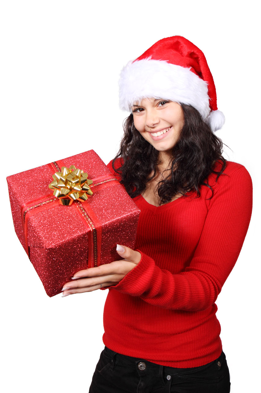 a beautiful young woman with a christmas present free stock photo