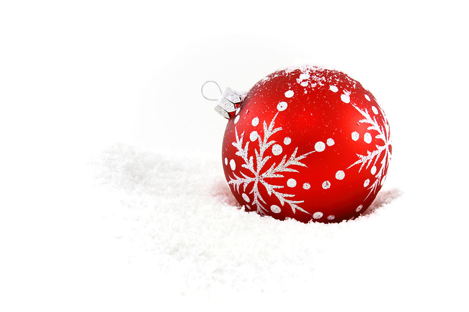 A red Christmas ornament in the snow.