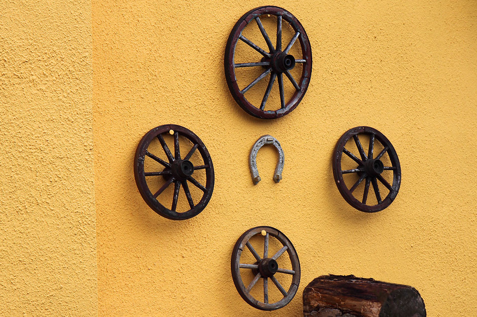 Old wooden cart wheels on the wall : Free Stock Photo